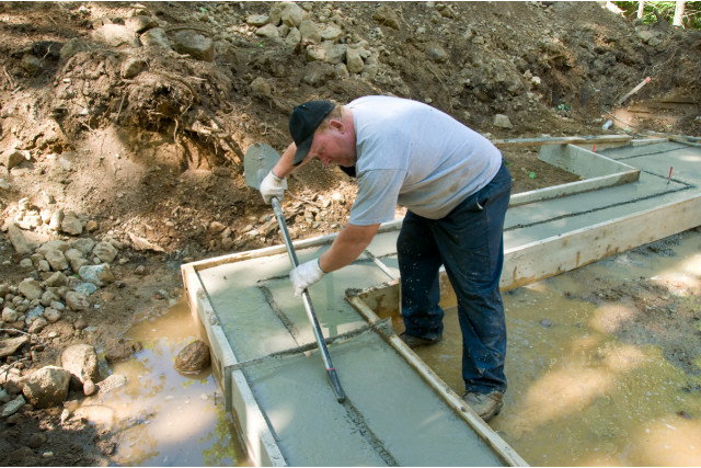 Worker leveling concrete foundation with a shovel